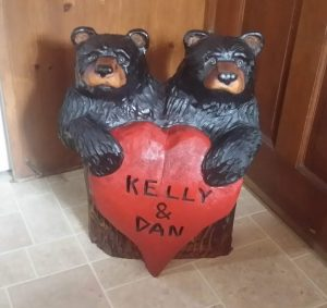chainsaw carved bears holding heart
